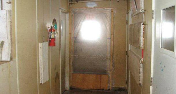 """Ejemplo de puerta sellada que previene la entrada de aire no deseado y convenientemente el movimiento no deseado de personal entre la zona """"limpia"""" (dentro de la granja) y zona """"sucia"""" (exterior de la granja)."""