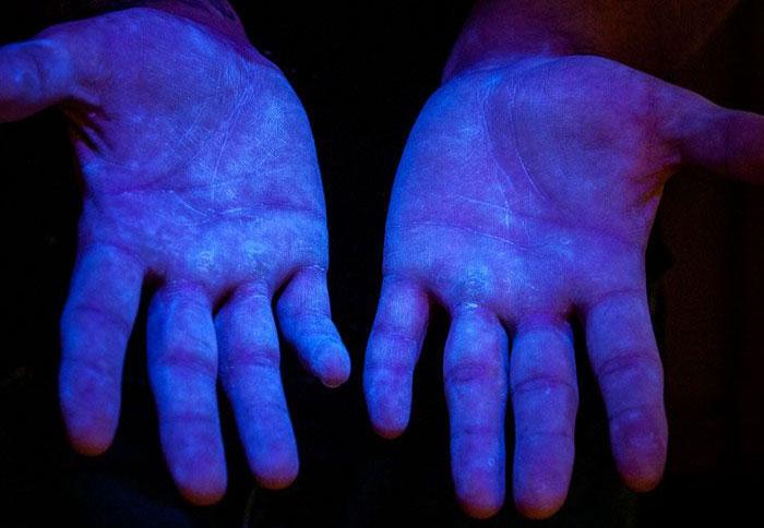 Foto 6. Material fluorescente bajo la luz ultravioleta (UV) para demostrar que el producto cubre la totalidad de las manos. Fuente www.glogerm.com
