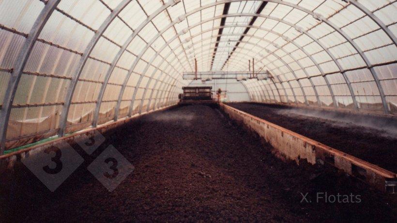 Figura 2. Sistema de compostaje en un invernadero, para evitar humectación por agua de lluvia y controlar la temperatura, con mezclado y aireación mediante máquina que circula sobre rieles en las paredes laterales. El material estructurante, que aporta carbono y porosidad, es paja de trigo.